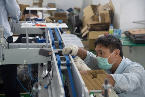 A technician is seen inspecting a face mask machine at a machine tool manufacturing plant in New Taipei. CNA photo March 21, 2020