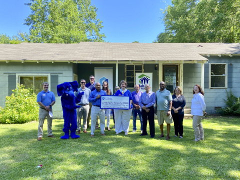 Citizens National Bank, in conjunction with the Federal Home Loan Bank of Dallas, awarded Lauderdale County Habitat for Humanity a $12,000 Partnership Grant Program grant. Tra Alford (left), community development director of Citizens National Bank and Monica Bradley (right), executive director of Lauderdale County Habitat for Humanity, hold the check. They were accompanied by staff members and volunteers upon receiving the award. (Photo: Business Wire)