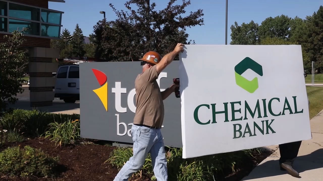 Universal Sign workers exchange Chemical Bank sign for TCF sign at banking center location in Southfield, Michigan on Friday, August 7th.