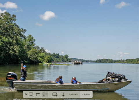 Kathleen Gibi, Executive Director, Keep the Tennessee River Beautiful, and volunteers use a Yamaha V MAX SHO-powered work boat to remove trash and debris from the Tennessee River. (Photo: Business Wire)