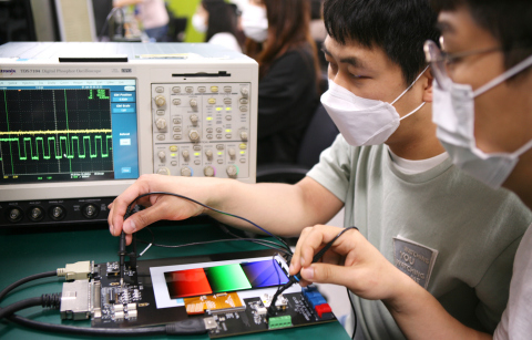 Engineers from Samsung Display are using testing devices to inspect frequency changes in display panels that feature adaptive frequency technology (Photo: Business Wire)