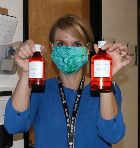 An employee of Covetrus, an animal-health technology and services company, holds two of the 6,000 bottles of hand sanitizer that Covetrus pharmacists made at the Company's pharmacy compounding facility in Phoenix. The hand sanitizer has been donated for use by nonprofit organizations and healthcare workers. (Photo: Business Wire)