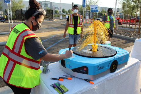 Associates from the new fulfillment center in Beaumont, California sign an Amazon robot to commemorate the launch of the new building. (Photo: Business Wire)