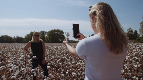 "Katy Powers takes a photo of Sydney Parker in the middle of a cotton field at Grant Farms in Garysburg, North Carolina. The North Carolina State University students are featured in the ""Crop to Campus"" documentary about T-shirt sustainability. (Photo: Business Wire)"