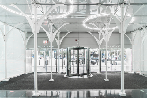 Urban Umbrella's flagship product is a revolutionary, cross-bracing-free sidewalk shed composed of high-strength steel, translucent plastic panels, LED lighting, and white arching struts that combine the strength of a highway bridge and the beauty of a work of art (Photo: Business Wire)