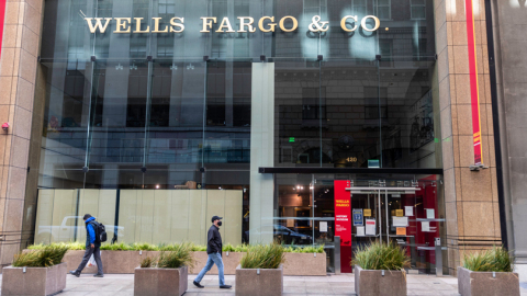 External view of Wells Fargo building with a glass front and individuals walking by on sidewalk. (Photo: Business Wire)