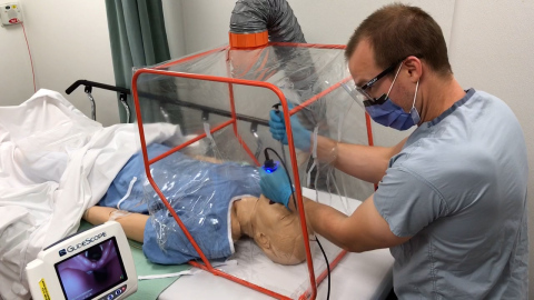 Dr. Marc Curial demonstrates use of the portable Aerosol Containment Tent (ACT) on a mannequin. (Photo: Business Wire)