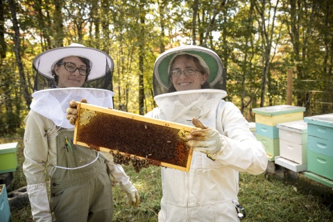 Beekeepers Colleen Fitts and Raine Nimmer tend to their beehives. (Photo: Business Wire)
