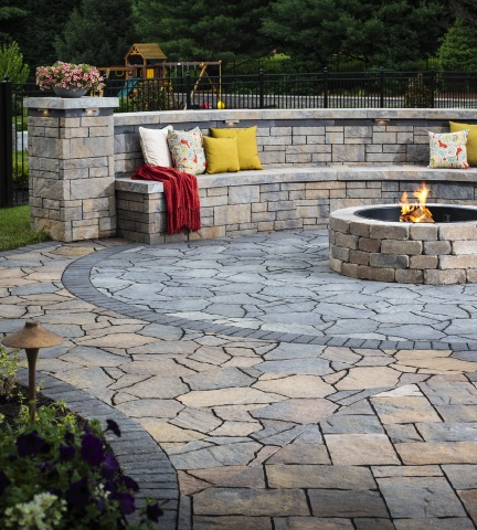 Belgard outdoor living featuring Mega-Lafitt® Paver, Tandem™ Wall and Weston Stone™ Fire Pit with Color of the Year, Marigold, as an accent color. (Photo: Business Wire)
