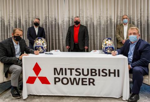 Jim Heilbron (izq.), vicepresidente sénior y director de Producción Principal de Alabama Power, y Paul Browning, presidente y director ejecutivo de Mitsubishi Power, celebran la designación de JAC con una tradición de firma japonesa. (Crédito: Mitsubishi Power)