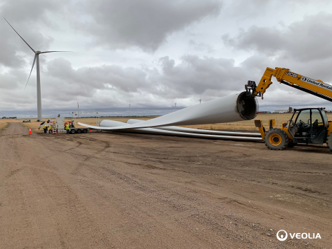 A wind turbine blade being prepared for removal after it has reached the end of its life cycle, with a nearby wind turbine in the backdrop. Blades like these are now being repurposed by Veolia North America after reaching the end of their life cycle, which typically lasts about 20 years. (Photo: Business Wire)