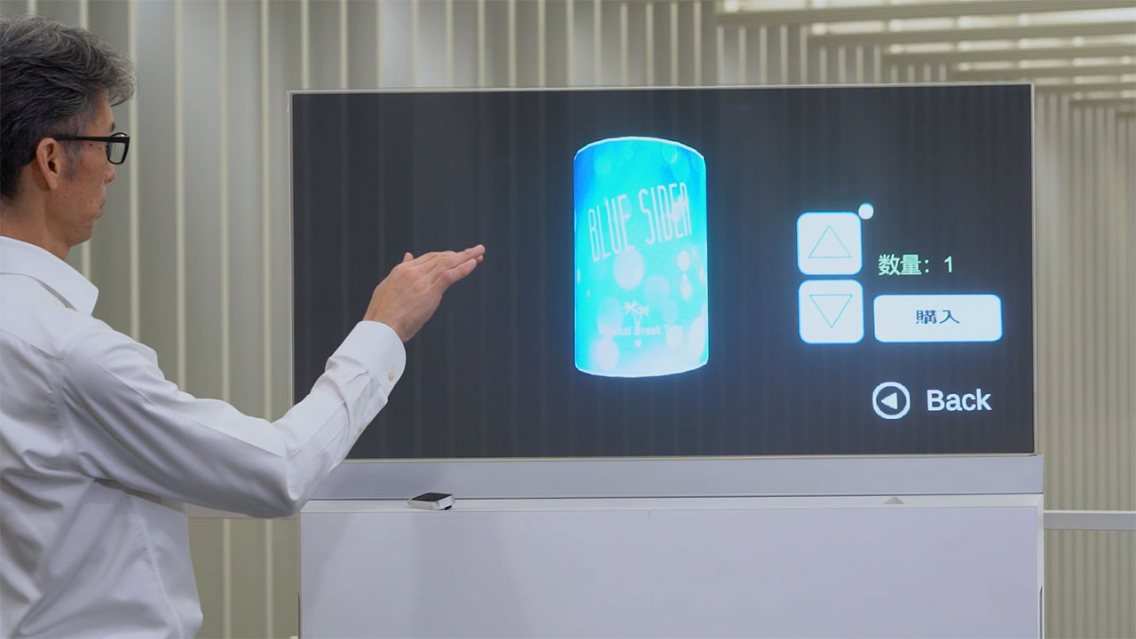 DNP has developed a new transparent display screen that can be operated in a touchless format, by merely moving a hand over a motion sensor. A liquid crystal light control film is attached to a transparent screen facilitating a variety of video expressions on a single screen, from standard displays to augmented reality (AR) driven effects, including those where vivid images appear to hang in the air.