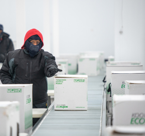 A worker at McKesson's Olive Branch, Miss. distribution center prepares packed and sealed cooler boxes containing Moderna COVID-19 vaccine doses for shipment. (Photo: Business Wire)