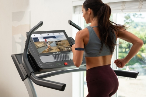 An iFit user wears the iFit SmartBeat forearm heart rate monitor, while ActivePulse technology automatically adjusts the treadmill's speed and incline to keep her in the optimal heart rate zone. (Photo: Business Wire)