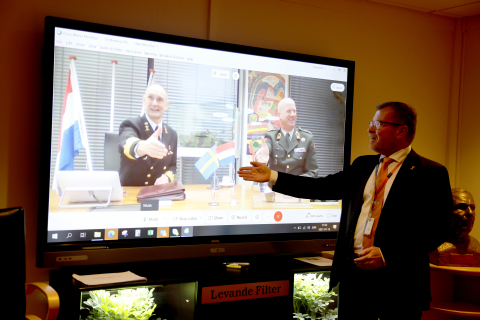 Admiral Arie Jan de Waard and Lieutenant General Martin Wijnen of the Royal Netherlands Army seal the deal via digital handshake with Tommy Gustafsson-Rask, managing director of BAE Systems Hägglunds. (Photo credit: BAE Systems)