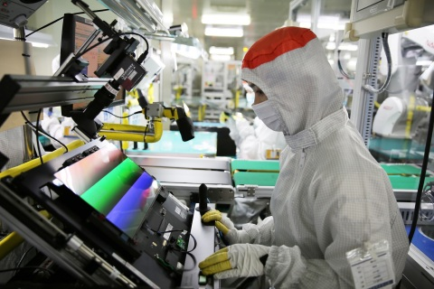 Samsung Display production technician with advanced OLED display equipment (Photo: Business Wire)