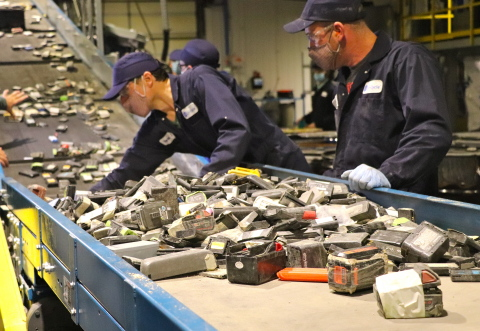 Li-Cycle employees feed lithium-ion batteries into the shredder at Kingston, ON facility