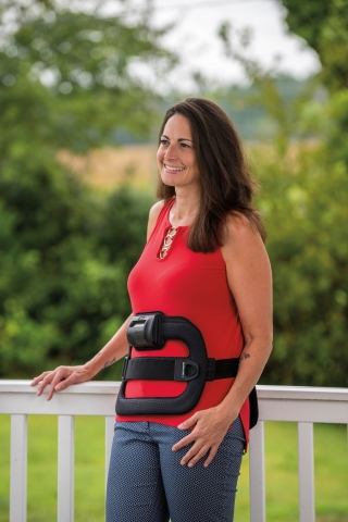 Orthofix is the first and only company in the U.S. to offer a free recycling program so patients can properly dispose of their Bone Growth Therapy devices after use. The innovative program enables Orthofix patients like triathlete Tamie (pictured here wearing her SpinalStim™ device) to recycle their devices for non-medical use once they complete treatment. (Photo: Business Wire)