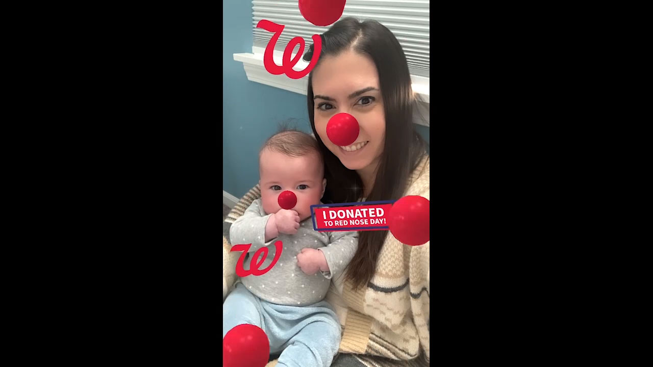 Woman and baby show off Digital Red Nose in support of Red Nose Day.
