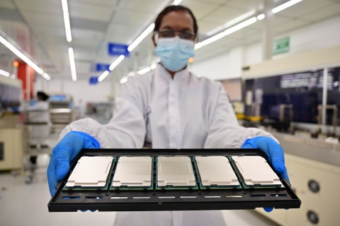 """Intel manufacturing technicians in Kulim, Malaysia, display 3rd Gen Intel Xeon Scalable processors during their production cycle. Intel introduces the 3rd Gen Intel Xeon Scalable processors (code-named """"Ice Lake"""") and the full platform that they join on Tuesday, April 6, 2021. (Credit: Jason Cheah/Intel Corporation)"""