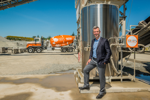 CarbonCure CEO and Founder Rob Niven standing with a CarbonCure system and branded concrete truck (Photo: Business Wire)