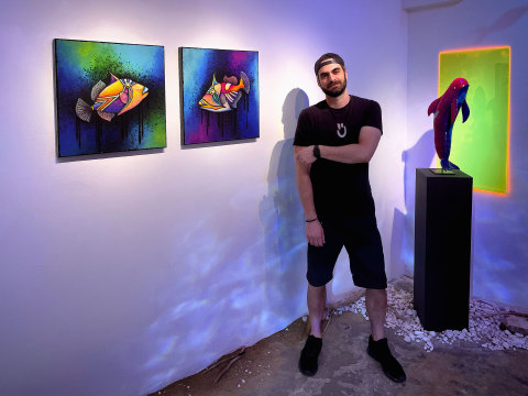 The artist Sküt, standing between his triggerfish and Bubbles, in the glow of his immersive installation. [Photo Credit: Dex Franco]