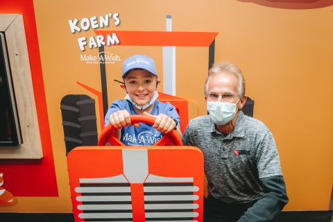 """Make-A-Wish wish recipient Koen poses for a picture with Sioux Falls Tractor Supply Store Manager, Randy Schall, while exploring """"Koen's Farm"""", an interactive farming exhibit in the waiting room at Avera Medical Group Pediatric Specialists in Sioux Falls, S.D. Photo credit: Danny Eisenhauer Photo."""