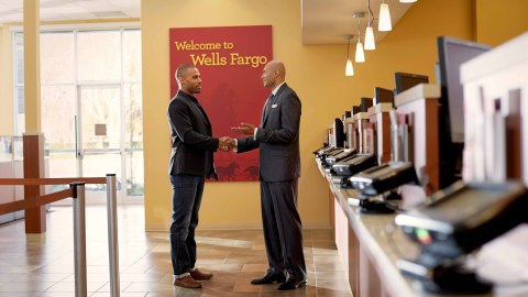 Male Wells Fargo employee shaking hands with another male in front of a teller line. (Photo: Wells Fargo)