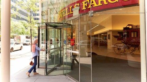 Woman entering a Wells Fargo branch with a glass front through a revolving door. (Photo: Wells Fargo)