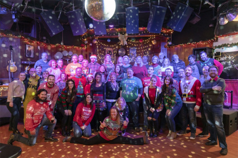 Staffers from DirectEmployers Family of Brands strike a pose at the organization's 2019 Holiday Party, which featured an afternoon of karaoke, dancing, and connection at Howl at the Moon in downtown Indianapolis, Indiana. (Photo: Business Wire)