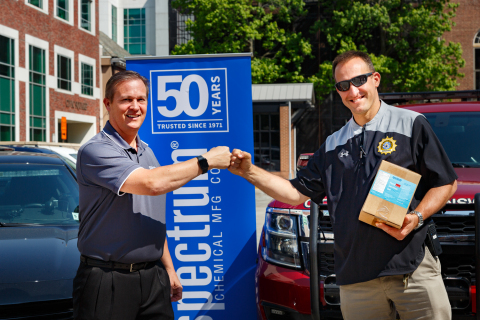 Spectrum Chemical COO Russell Kneipp and New Brunswick Police Sergeant Thierry Lemmerling fist bump over Spectrum PPE donations to the New Brunswick, NJ police and fire departments.(Photo: Business Wire)