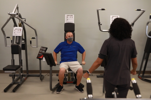 Optum employee demonstrates the new gym equipment during the grand opening event for Optum-Hemet Clinic and Community Center. Credit: Sandy Huffaker