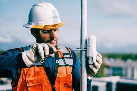 An Alaska Communications field technician installs a customer node on a rooftop in Anchorage, Alaska. (Photo: Christophe Wu, Facebook)