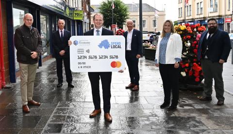 Photo prise à Carrickfergus, comté d'Antrim : À l'extrême gauche, Lee Britton, PDG Europe d'EML, au centre avec une carte, Gordon Lyons, Ministre de l'Économie d'Irlande du Nord, et en deuxième position à partir de la droite, Sarah Cunningham, Vice-présidente et Responsable de la Plateforme technologique de Dublin de Mastercard. (Photo : Business Wire)