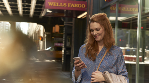 A woman looks at her phone with Wells Fargo sign in background (Photo: Wells Fargo)